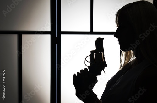 Silhouette of fashion killer woman with revolver pistol Canvas Print