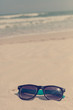 Sunglasses in the sand on the seashore. vacation time