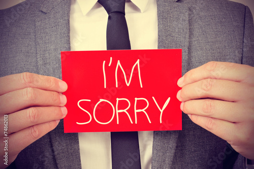 man with signboard with the text I am sorry Canvas Print