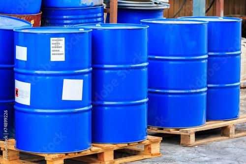 Fotografia  Big blue barrels on wooden pallets
