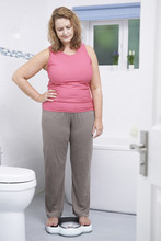 Overweight Woman Weighing Herself On Scales In Bathroom