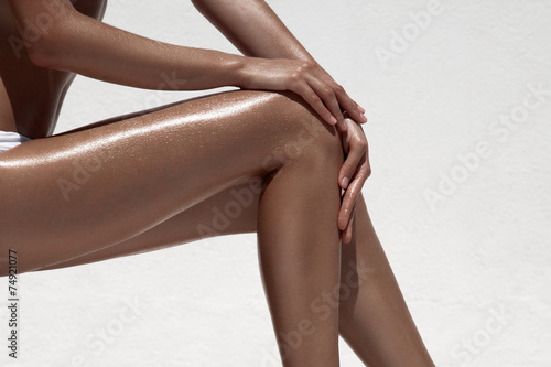 Beautiful woman tan legs. Against white wall.