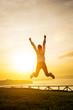 Happy female athlete jumping towards the sun