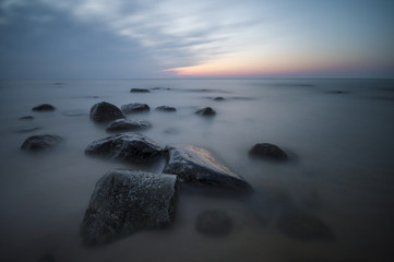 Fototapetamorskie głazy na plaży po zachodzie słońca