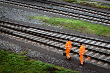 Two Workers Walking Along Rail...