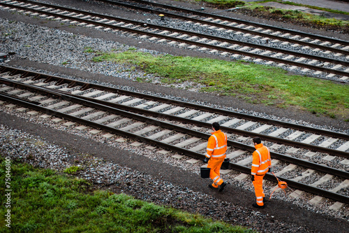 Tuinposter Spoorlijn Two workers walking along railroad tracks