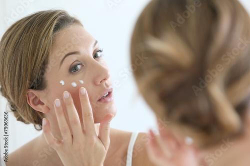Obraz na plátně  Middle-aged woman applying anti-aging cream