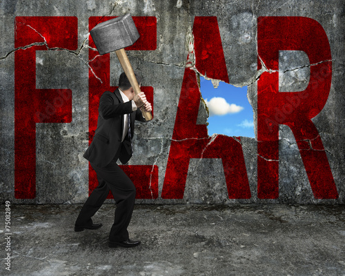 Photo  businessman holding hammer hitting red FEAR word on concrete wal