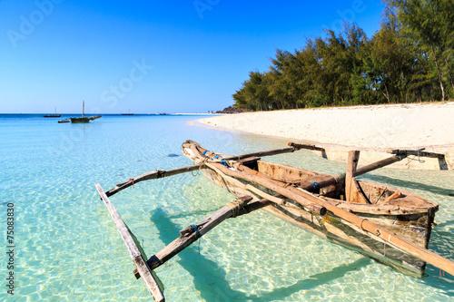 Poster Zanzibar Traditional fisherman boat lying near the beach in clear water