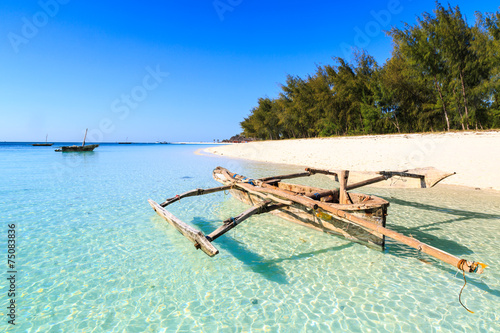 Spoed Foto op Canvas Zanzibar Traditional fisherman boat lying near the beach in clear water