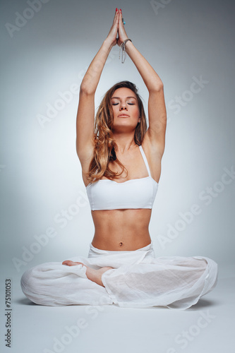Fényképezés  Young woman in yoga pose in studio on white background