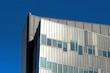 New modern office building with aluminum grey facade against de