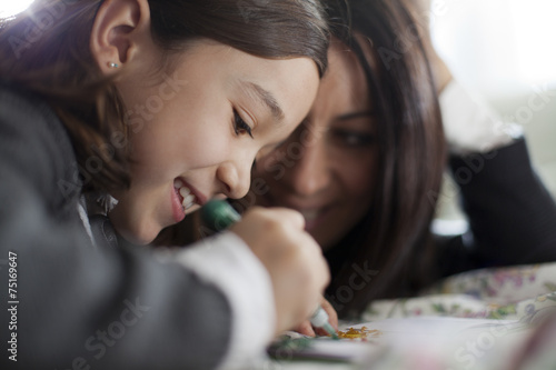 Niña dibujando mientras su madre la observa Canvas Print