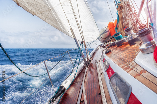 Платно  sail boat navigating on the waves