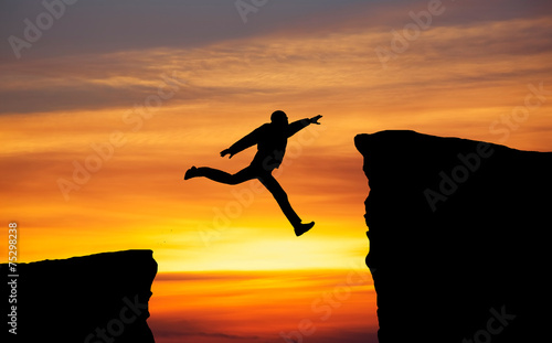 Foto Man jumping across the gap from one rock to cling to the other.