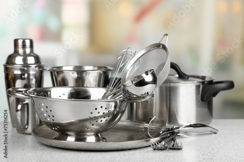 Fotografia  Stainless steel kitchenware on table, on light background