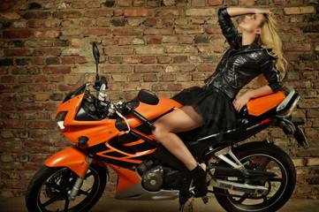 Obraz na płótnie Canvas Hübsche junge Frau posiert auf Motorrad