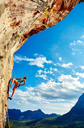 Fototapeta Rock climber climbing up a cliff obraz