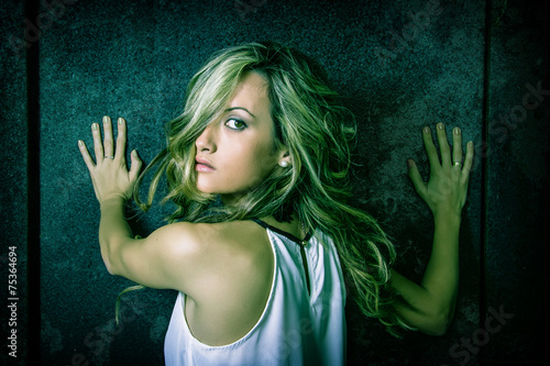 Photo  Young woman scared with her hands over a metallic door