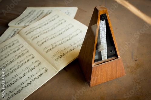 Wooden metronome sets the rhythm by swinging pendulum #75393828