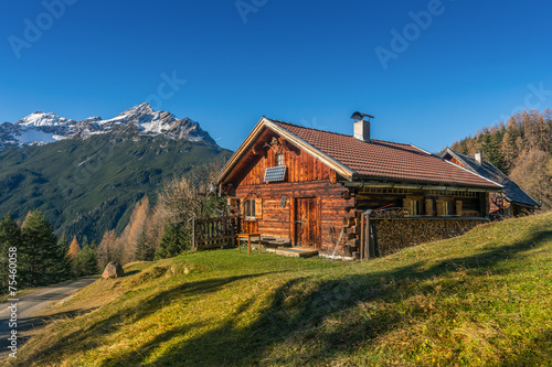 Fototapeta old wooden hut cabin in mountain alps at rural fall landscape