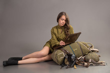 Girl In Soviet Army Uniform Sits On Parachute With Bag Board