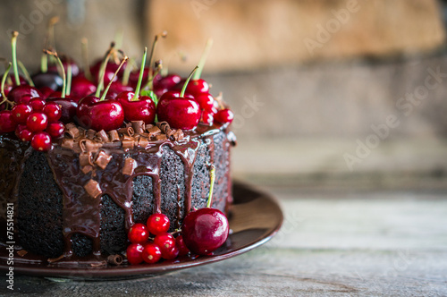 Fényképezés  Chocolate cake with cherries on wooden background