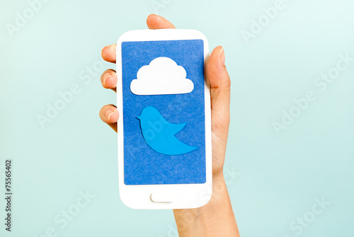 Obraz Conceptual phone showing a cloud and bluebird on blue background - fototapety do salonu