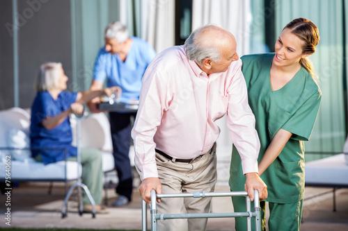 Fotografia  Happy Caretaker Assisting Senior Man In Using Zimmer Frame