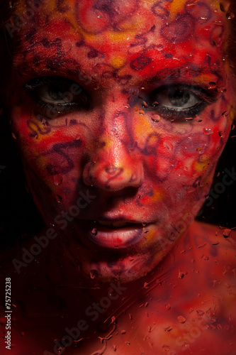 Fashion Model Portrait with red face art. Body art.Paint on face