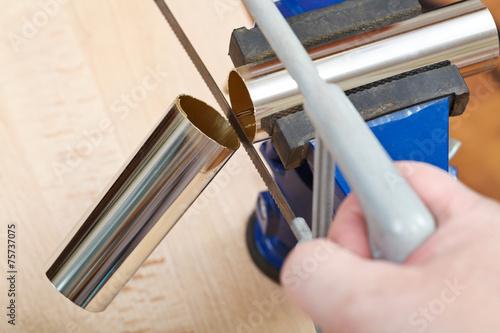 Valokuva  mechanic saws chrome plated drain pipe close up