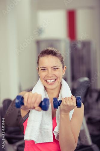 lachende frau trainiert mit gewichten