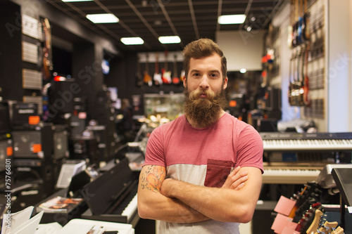 Deurstickers Muziekwinkel assistant or customer with beard at music store
