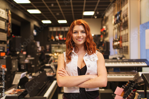 Deurstickers Muziekwinkel smiling assistant or customer at music store