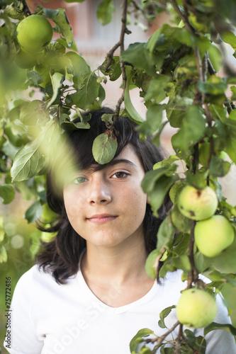 Valokuva  Dark-haired teen girl in the apple orchard.