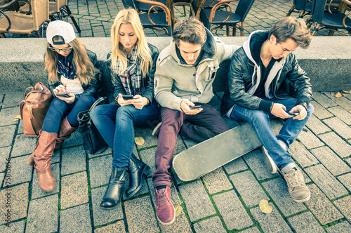 Fotografie, Obraz  Group of young hipster friends playing with smartphone