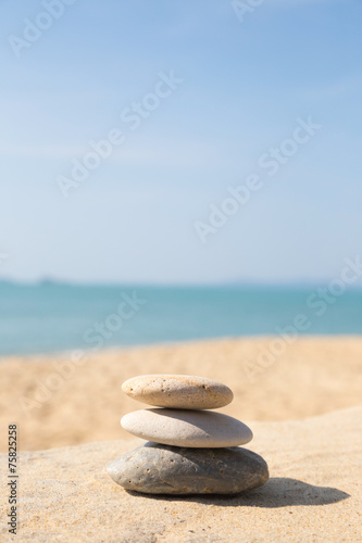 Photo Stands Stones in Sand Stones balance, pebbles stack on sunny sea beach