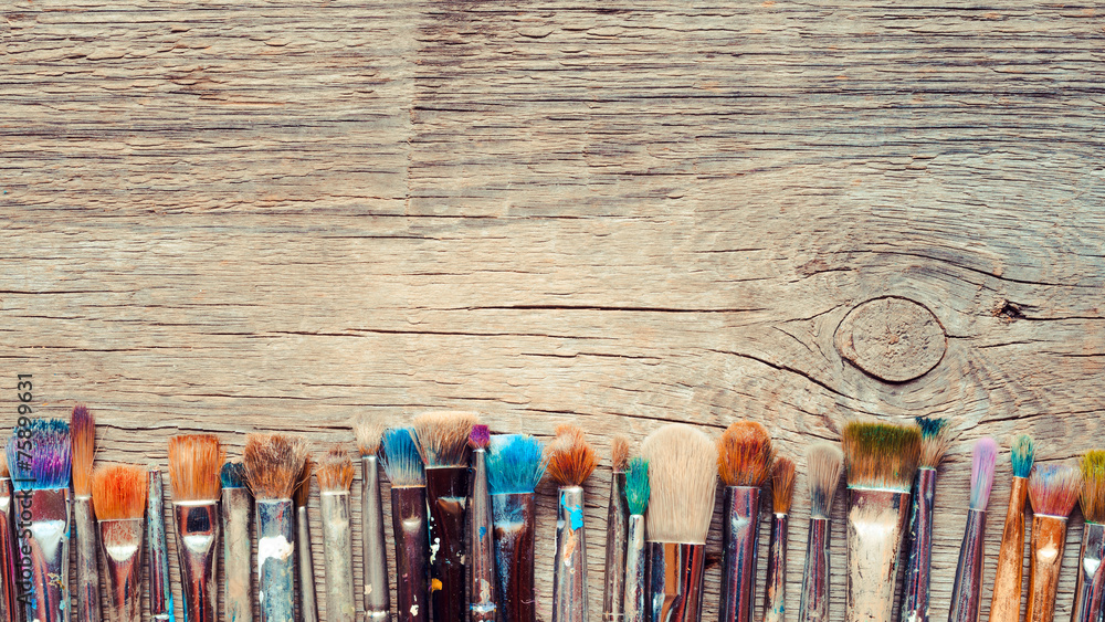 Fototapeta Row of artist paintbrushes closeup on old wooden rustic backgrou