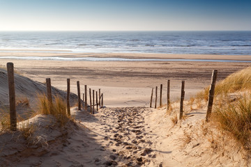 Fototapeta sand path to North sea at sunset