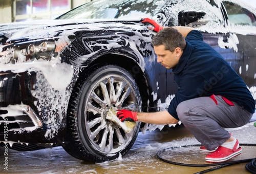 Fotografía  Man worker washing car's alloy wheels on a car wash