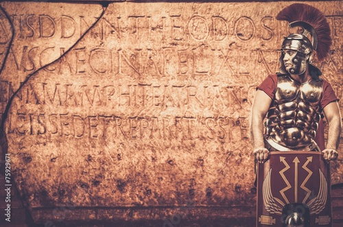 Fotografia Roman legionary soldier in front of  wall with ancient writing