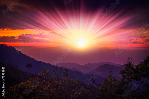 mountians and colour of sunrise,sunset behind light clouds