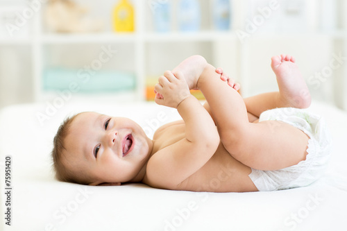 Fotografiet  baby lying on white bed and holding legs