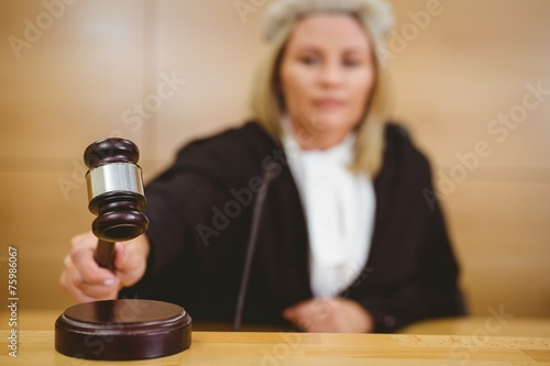 Fotografering  Serious judge with a gavel wearing robes and wig
