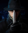 Man with a knife, studio shot, dark background