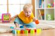 Leinwandbild Motiv child toddler playing wooden toys at home