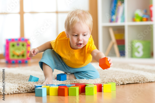 Obraz child toddler playing wooden toys at home - fototapety do salonu