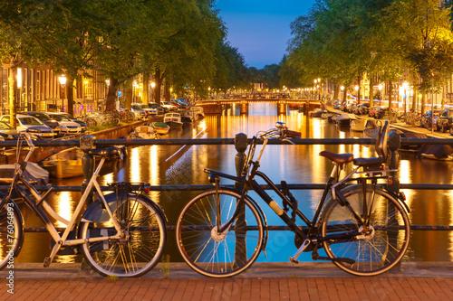 Photo  Night  illumination of Amsterdam canal and bridge