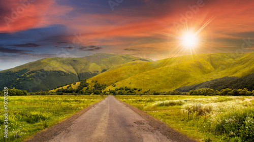 Foto op Canvas Baksteen abandoned road through meadows in mountain at sunset