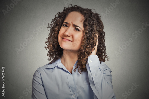 Skeptic. Doubtful woman looking at you grey background Poster